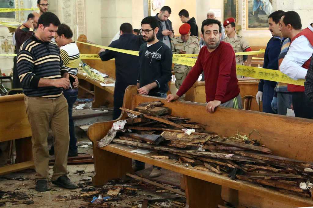 A general view shows forensics collecting evidence at the site of a bomb blast which struck worshippers gathering to celebrate Palm Sunday at the Mar Girgis Coptic Church in the Nile Delta City of Tanta (Photo credit: STRINGER/AFP/Getty Images)