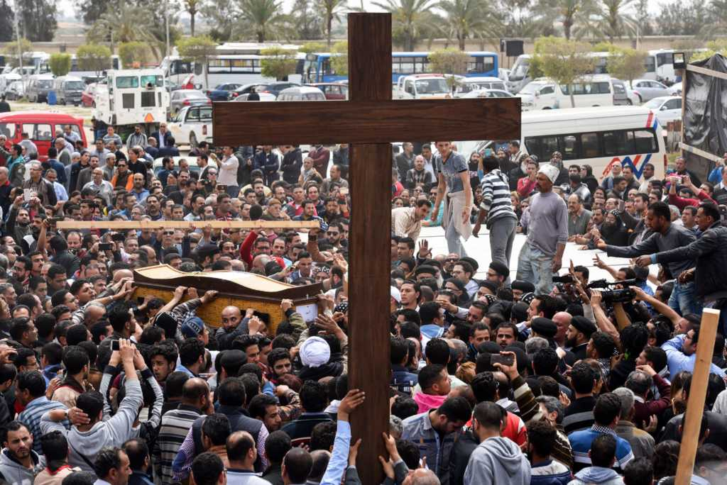 Mourners carry a large cross and the coffin of one of the victims of the blast at the Coptic Christian Saint Mark's church (Photo credit: MOHAMED EL-SHAHED/AFP/Getty Images)