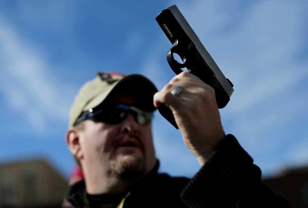 DALLAS, TX - JANUARY 19: Second Amendment supporter and gun enthusiast Derek Ringley displays an unloaded pistol that was being sold in an impromptu auction across the street from a gun buy back program at the First Presbyterian Church of Dallas on January 19, 2013 in Dallas, Texas. U.S. President Barack Obama recently unveiled a package of gun control proposals that include universal background checks and bans on assault weapons and high-capacity magazines. (Photo by Tom Pennington/Getty Images)