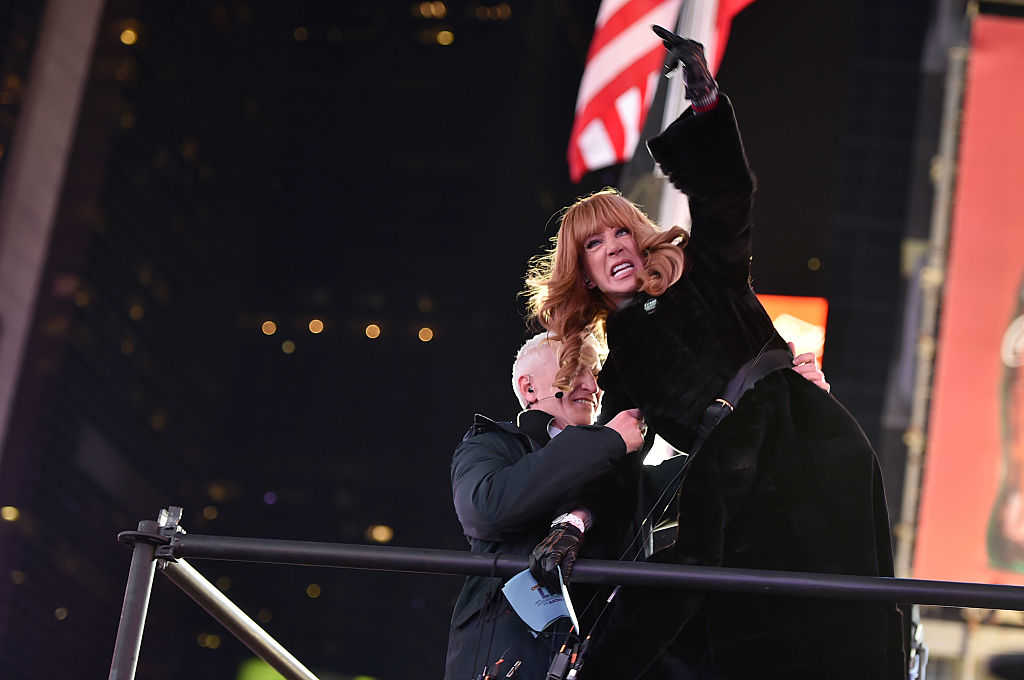 Kathy Griffin Yells at Ryan Seacrest from the media riser while Anderson Cooper restrains her (Theo Wargo/Getty Images)