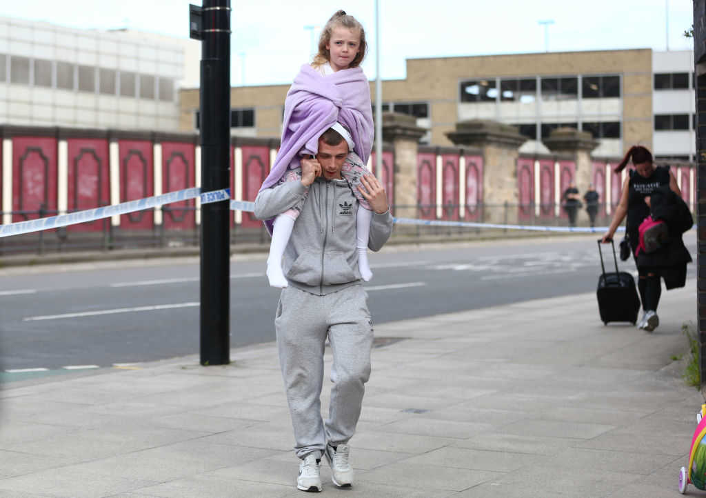 MANCHESTER, ENGLAND - MAY 23: A man carries a young girl on his shoulders on May 23, 2017 in Manchester, England. An explosion occurred at Manchester Arena as concert goers were leaving the venue after Ariana Grande had performed. Greater Manchester Police are treating the explosion as a terrorist attack and have confirmed 22 fatalities and 59 injured. (Photo by Dave Thompson/Getty Images)