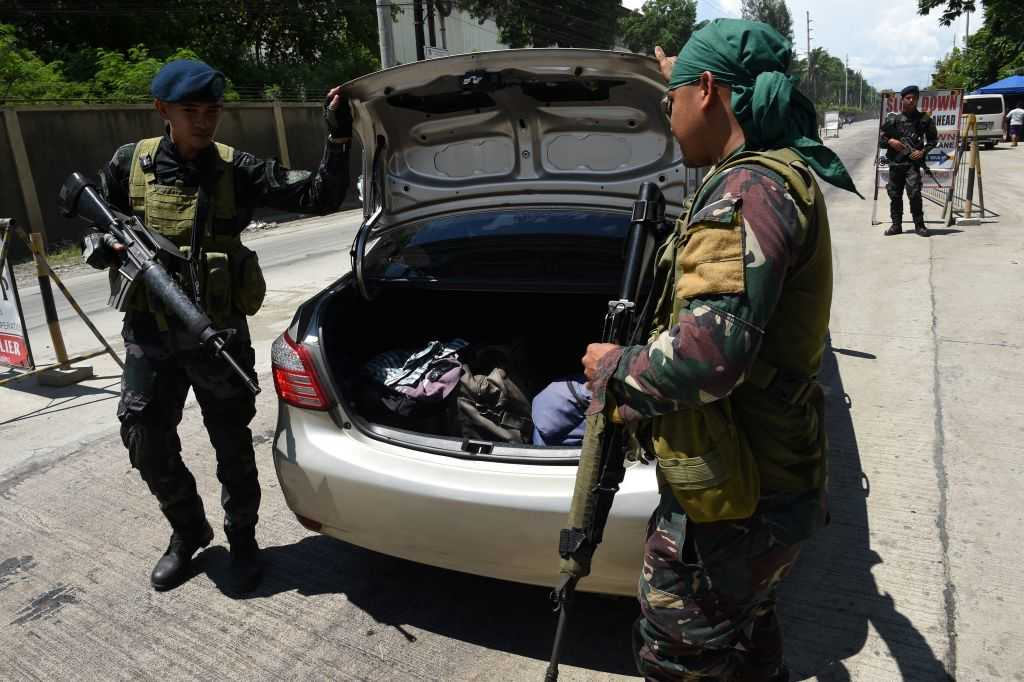 """Philippine policemen check a car boot of a resident fleeing from Marawi city, where gunmen who had declared allegiance to the Islamic State group rampaged through the southern city, at a checkpoint in Iligan City, in southern island of Mindanao on May 24, 2017. Philippine President Rodrigo Duterte warned that martial law would be """"harsh"""" and like a dictatorship, after imposing military rule in the south of the country to combat Islamist militants. / AFP PHOTO / TED ALJIBE (Photo credit should read TED ALJIBE/AFP/Getty Images)"""