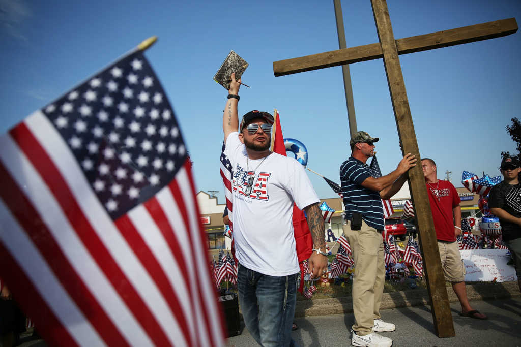 CHATTANOOGA, TN - JULY 19 : Evangelist Andrew Green from the Highways and Hedges Ministry preaches near the Armed Forces Career Center/National Guard Recruitment Office which had been shot up on July 19, 2015 in Chattanooga, Tennessee. . The gunman Mohammod Youssuf Abdulazeez, 24, opened fire on the military recruiting station at the strip mall on July 16th and then drove more than seven miles away to an operational support center operated by the U.S. Navy and killed four United States Marines and a Navy sailor. The gunman was likely killed in a exchange of gunfire with the police. (Photo by Joe Raedle/Getty Images)