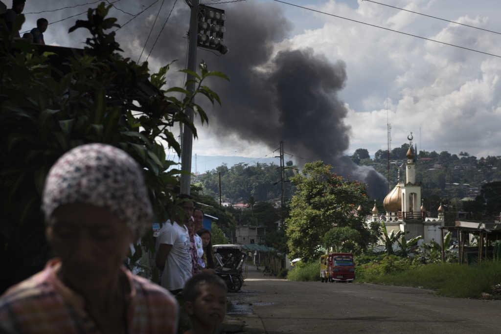 MARAWI CITY, PHILIPPINES - MAY 30: Smoke billows from the city center after an air attack by Philippine government troops on May 30, 2017 in Marawi city, southern Philippines. Philippine government troops are battling their way as they inch towards the city center where ISIS-linked militants have been holed for nearly a week. The fighting at Marawi city had forced around 85,000 people to seek refuge at evacuation centers in Marawi as the week long gun battles between ISIS-linked militants and security troops rose to around 100 with at least 19 civilians being killed in the fighting, according to local media. Filipino authorities announced around 2,000 people had been stranded amid street battles and air strikes while bodies of foreign Islamist militants were discovered during the ongoing battles in the southern city. President Rodrigo Duterte had declared 60 days of martial law in Mindanao on Tuesday after local terrorist groups Maute Group and Abu Sayyaf rampaged through Marawi city and said that martial law could be extended across the Philippines while thousands of residents continue to flee the crisis in Marawi, which is home to some 200,000 people. Jes Aznar/Getty Images