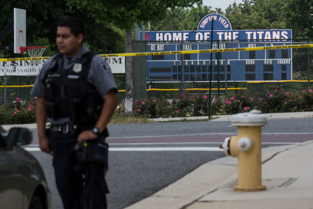 A police officer stands near Eugene Simpson Field, the site where a gunman opened fire June 14, 2017 in Alexandria, Virginia. Multiple injuries were reported from the instance, the site where a congressional baseball team was holding an early morning practice, including House Republican Whip Steve Scalise (R-LA) who was reportedly shot in the hip. (Zach Gibson/Getty Images)