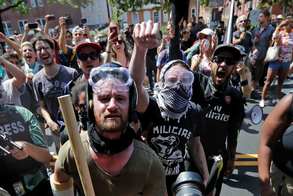 """Anti-fascist counter-protesters wait outside Emancipation Park to hurl insluts as white nationalists, neo-Nazis and members of the """"alt-right"""" are forced out after the """"Unite the Right"""" rally was declared an unlawful gathering August 12, 2017 in Charlottesville, Virginia. After clashes with anti-fascist protesters and police the rally was declared an unlawful gathering and people were forced out of Emancipation Park, where a statue of Confederate General Robert E. Lee is slated to be removed. (Chip Somodevilla/Getty Images)"""
