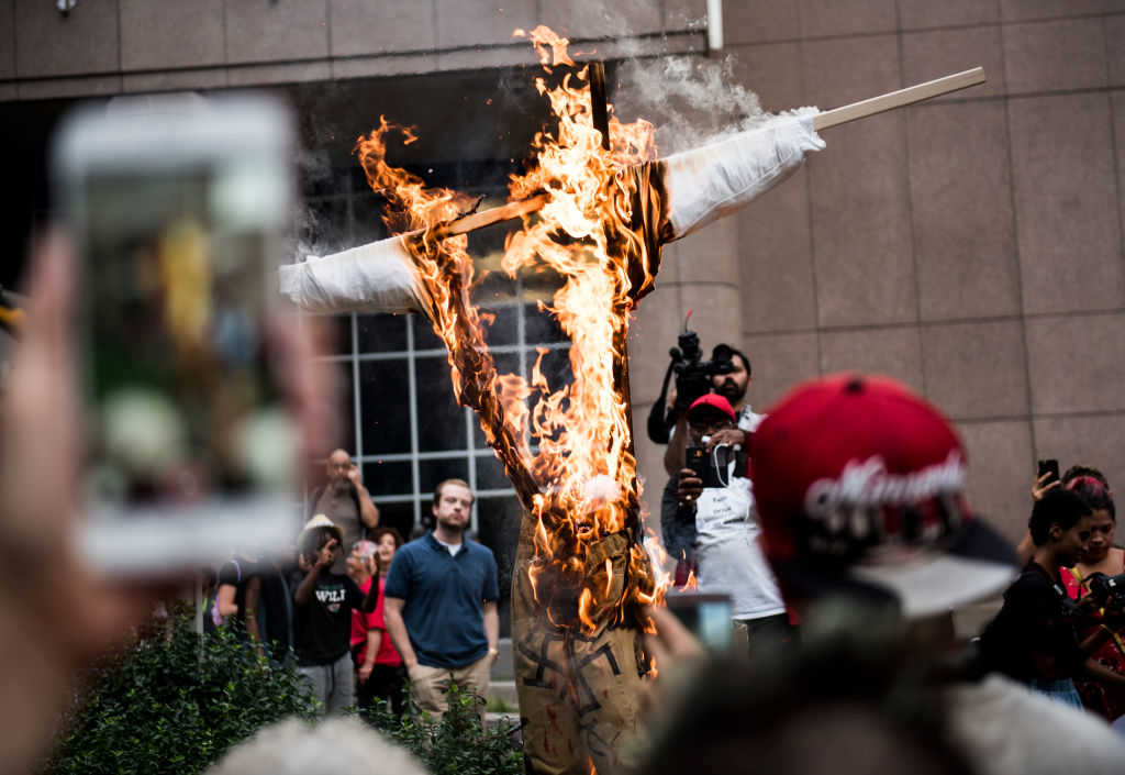 An effigy of U.S. President Donald Trump, dressed in khakis and a white shirt covered in swastikas, is set ablaze during a protest against racism and the violence over the weekend in Charlottesville, Virginia on August 14, 2017 in Minneapolis, Minnesota. (Stephen Maturen/Getty Images)