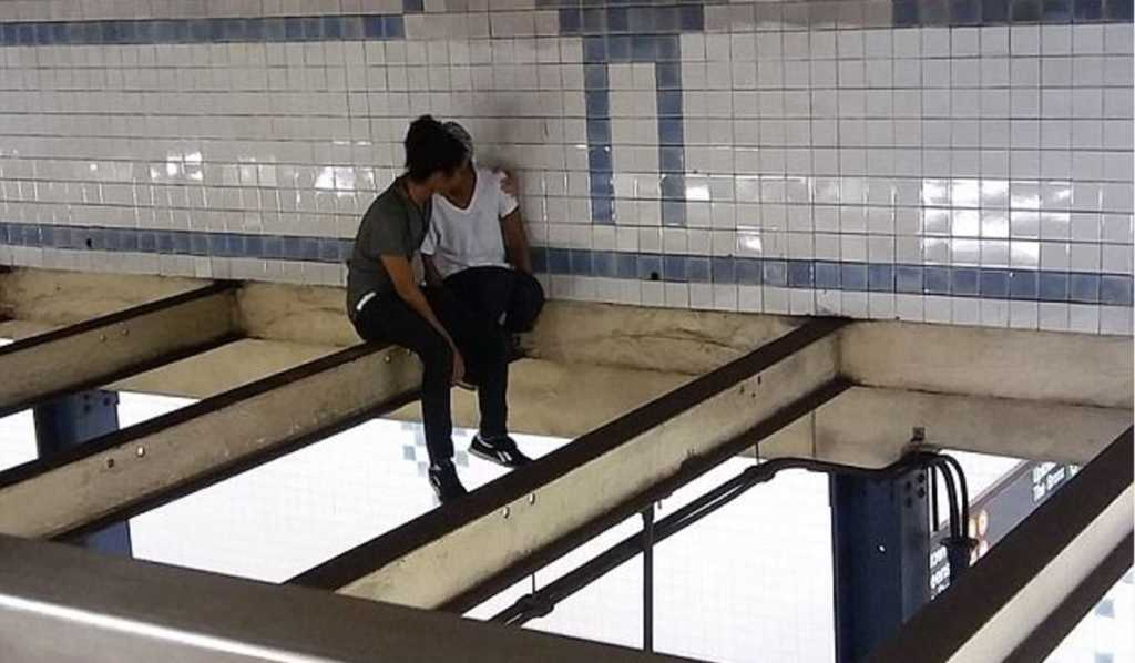 A man comforts a suicidal woman above NYC subway tracks. (Photo Credit: Michal Klein/Facebook)