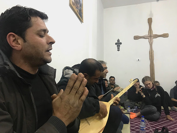 New Syrian Christians sing a prayer with traditional Kurdish guitar. (Photo credit: Free Burma Rangers)