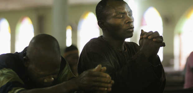 Nigerian Catholic worshippers pray during morning Mass April 12, 2005 in Kano, Nigeria. (Photo by Chris Hondros/Getty Images)