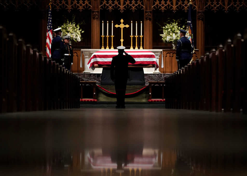 A member of the military salutes the flag-draped casket of former President George H.W. Bush as it lies in repose at St. Martin's Episcopal Church on December 5, 2018 in Houston, Texas. (Photo by David J. Phillip-Pool/Getty Images)