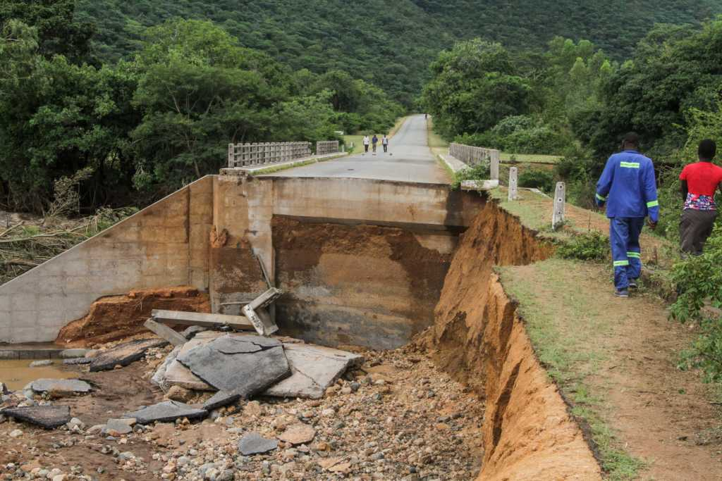 People cross one of several bridges destroyed by Cyclone Idai on March 19, 2019 in Chimanimani, Zimbabwe. (Photo by Tafadzwa Ufumeli/Getty Images)
