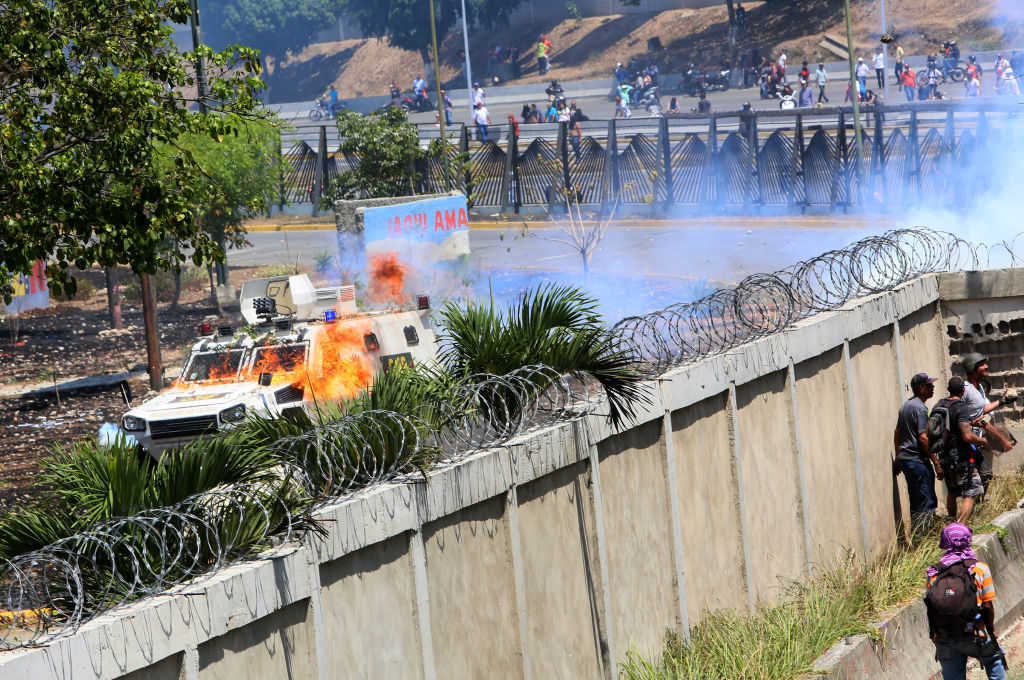 Demonstrators throw petrol bombs to military forces at the air force base La Carlota on April 30, 2019 in Caracas, Venezuela. (Photo by Edilzon Gamez/Getty Images)